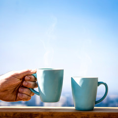 Wall Mural - Mug of blue colors with tea or coffee and city landscape with blue sky.