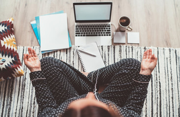 Businesswoman dressed in pajamas, listening earphones meditating with morning coffee with Gyan Mudra palm on floor office with laptop, papers top view shot. Distance work in quarantine time concept. Fotomurales