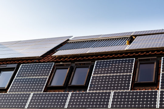 House with solar panels and solar panels for water heating on roof - regenerative energy system electricity generation