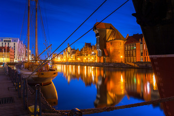 Old town in Gdansk with historical port crane over Motlawa river at night, Poland.