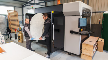 Technicians wear huge 3d model printed on large 3d printer