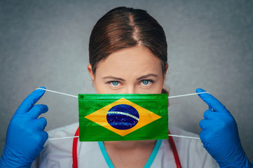 Coronavirus in Brazil Female Doctor Portrait hold protect Face surgical medical mask with Brazil National Flag. Illness, Virus Covid-19 in Brazil, concept photo
