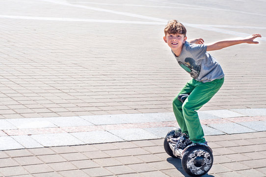 Fashionable teen boy rides a giroskuter in the city square. Fashion for gyro scooters and gyroboards among teenagers. Active children's leisure in the summer. Smart eco transport segway