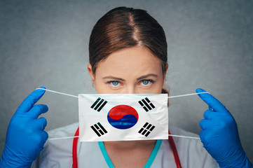 Coronavirus in South Korea Female Doctor Portrait hold protect Face surgical medical mask with South Korea National Flag. Illness, Virus Covid-19 in South Korea, concept photo