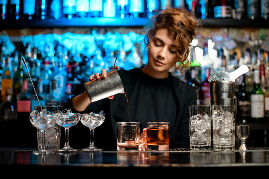 Young woman barman preparing cocktail and pouring it into glass.