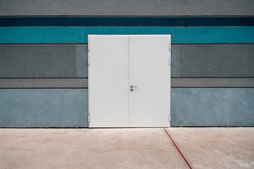 Exterior of a new blue concrete building with large closed white metal door