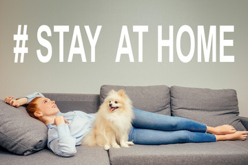 happy, redhaired ginger woman in shirt and jeans lying down with her white fluffy spitz have a rest on gray new folding sofa copyspase.need air conditioning. stay at home concept