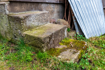 short stairs made of concrete and stone in the barn of an old farm