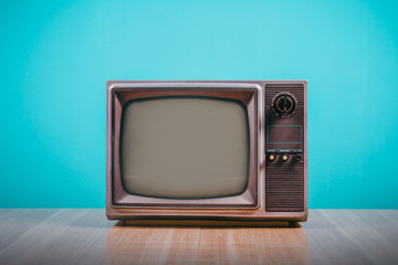 Retro old tv on wooden table with blue concrete wall background.
