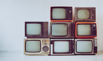 Pile of old retro television in room, vintage filter effect