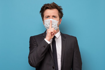 man in medical mask with shh gesture, asking for silence or to be quiet Fotomurales