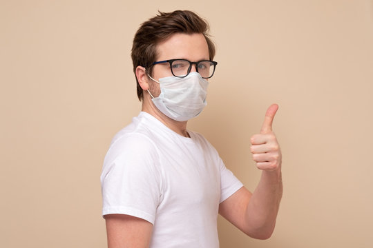 Caucasian young man showing thumb up with single use medical mask to prevent infection