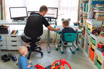 Father with kids working from home during quarantine. Stay at home, work from home concept during...
