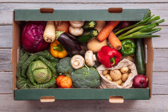 Fresh organic vegetable delivery box on a wooden background
