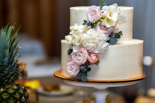 Tall sweet wedding cake decorated with live pink and white flowers on a table.