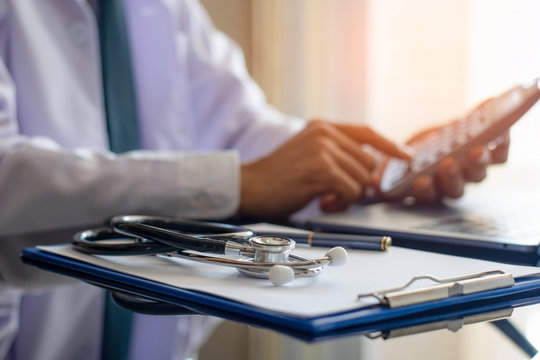 Male doctor hand using calculator for account about medical costs with stethoscope, clipboard and computer notebook on the desk at modern office at clinic. Healthcare costs and fees concept.
