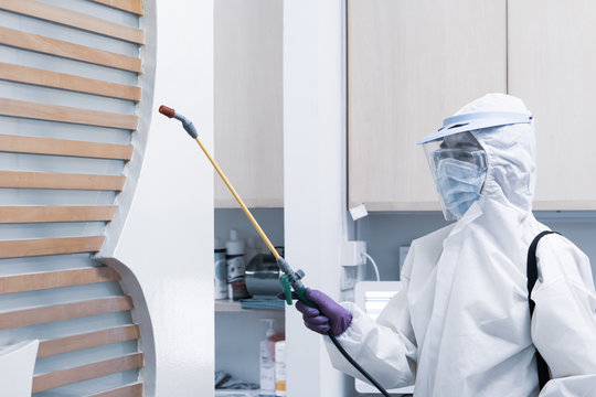 worker in personal protective equipment including white suit mask and face shield sparaying disinfectant to control coronavirus infection in the dentist clinic