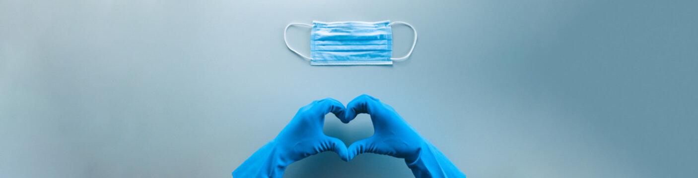 Coronavirus in Italia fine della pandemia, successo con simbolo del cuore fatto dalle mani di un medico. Virus definitivamente debellato. Vista panoramica. Banner.
