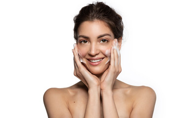 Fototapeta Nice woman with facial foaming cleanser looking at camera enjoys applying perfect fresh clean skincare cosmetics.