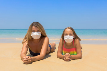 A woman and a child in a protective surgical mask on their face are standing on the beach in...