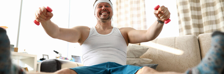Funny smiling man sitting on fit ball working out