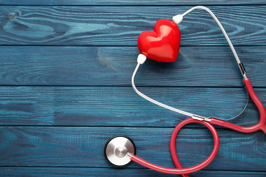 Stethoscope with red heart on blue wooden table
