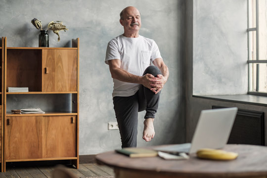 man doing yoga exercise at home using online lesson on notebook,