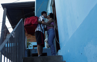 Erik Thiago kisses his wife before going to work, in Sao Paulo