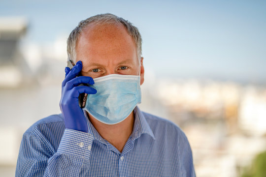 A man using protective masks and blue latex gloves while using mobile phone