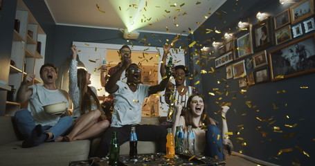 Happy multiethnic friends fans get crazy watching sports game at home, shout, celebrate win with confetti slow motion.