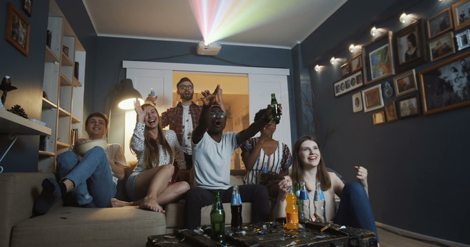 Happy diverse group of young fans watch sports game at home on TV with projector, all shout supporting slow motion.