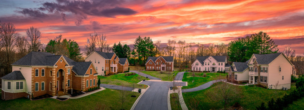 Neighborhood street sunset panorama of modern upper middle class single family houses American real estate in a new construction in Maryland USA colorful dramatic sky