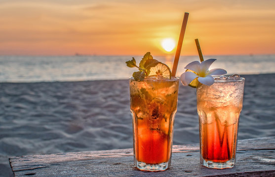 drinks with blur beach and sunset in background