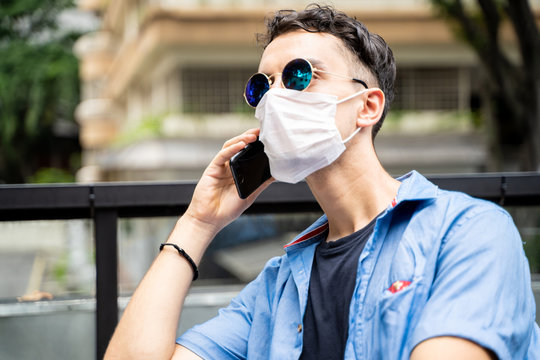 Man with face mask and sunglasses talking to his mobile phone on an outside