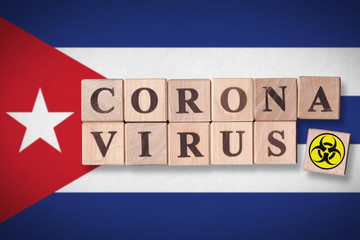 Papiers peints Amérique du Sud Cuba flag background and wooden blocks with letters spelling CORONAVIRUS and quarantine symbol on it. Novel Coronavirus (2019-nCoV) concept, for an outbreak occurs in Cuba.