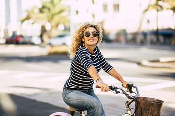 Beautiful and cheerful adult young woman enjoy bike ride in sunny urban outdoor leisure activity in the city - happy people portrait - trendy female outside having fun