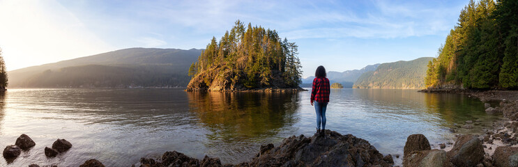 Girl Hiking in the Canadian Landscape during a vibrant winter sunset. Hike on Jug Island Trail in Belcarra, Vancouver, British Columbia, Canada. Nature Panorama Background Fototapete