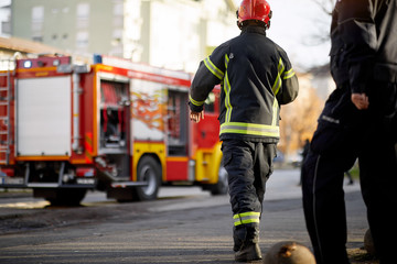 Fireman in uniform in front of fire truck going to rescue and protect. Emergancy servise concept.