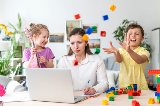 Young women works at home with laptop, along with children. Children make noise