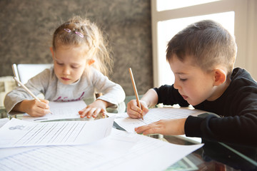 Schoolboy and schoolgirl writing letters. Close-up  pencil in the hand of child. Children learning to write letters at the table. A home distance learning.