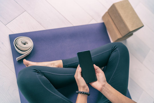 Phone online fitness class fit woman using mobile app at home for strength training workout videos in apartment looking at cellphone screen. Top view of exercise mat.