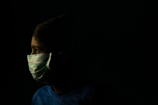 Low key photography of child with mask on face with a space for text