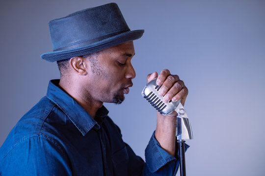 Portrait of a hipster attractive black man singing a vintage song. Isolated male performing ethnic cultural songs. Young african american singer holding trendy microphone. Compose and create lyrics.