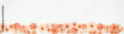 Mothers Day or spring bottom border of pink paper flowers. Top view over a white background. Copy space.
