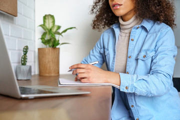 Young african american woman student e learning watching video training course sit at home office desk. Mixed race girl look at laptop computer study with online teacher making notes. Close up view