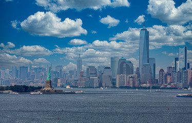 Fototapete - Statue of Liberty in New York Harbor with Manhattan skyline and Freedom Tower in background