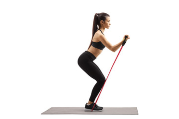 Full length profile shot of a young woman in sportswear exercising with a resistance band