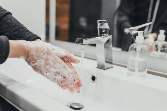 Washing hands with antibacterial soap at home bathroom for coronavirus prevention. Coronavirus pandemic protection by washing hands frequently. Hygiene to stop spreading coronavirus.
