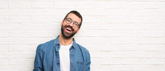 Handsome man with beard over white brick wall smiling