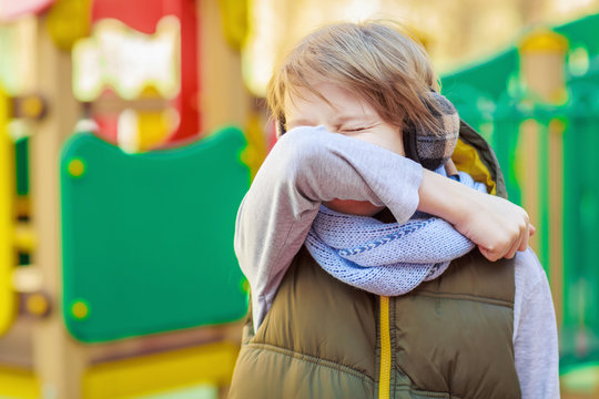 Schoolboy sneezing on arm elbow outdoor for protect from coronavirus